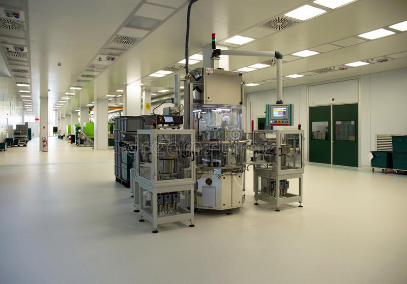 Injection molding of biomedical products in clean room. Injection molding (or moulding) of biomedical products in a large cleanroom. A cleanroom or clean room is stock photo