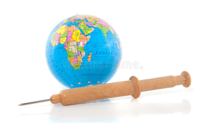 Injection needle. A wooden injection needle in front of a world globe isolated over white royalty free stock photo