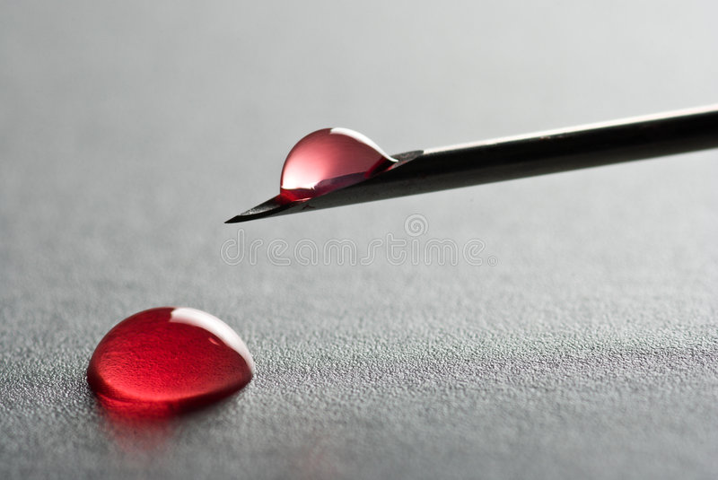Injection Needle. The Sharp point from a medical injection needle with a droplet of blood on gray surface stock image