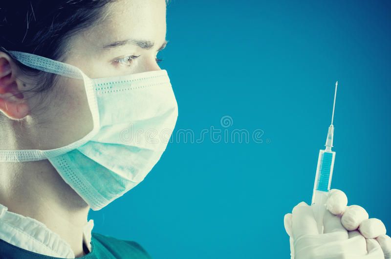 Injection ready to be administrated. Female doctor preparing to administrate an injection (landscape orientation with focus on needle pin and female eye royalty free stock image