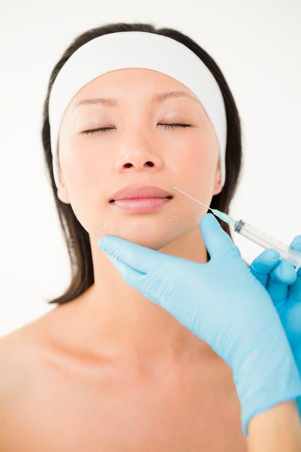 Injektion för kvinnahäleribotox på hennes kanter royaltyfri foto