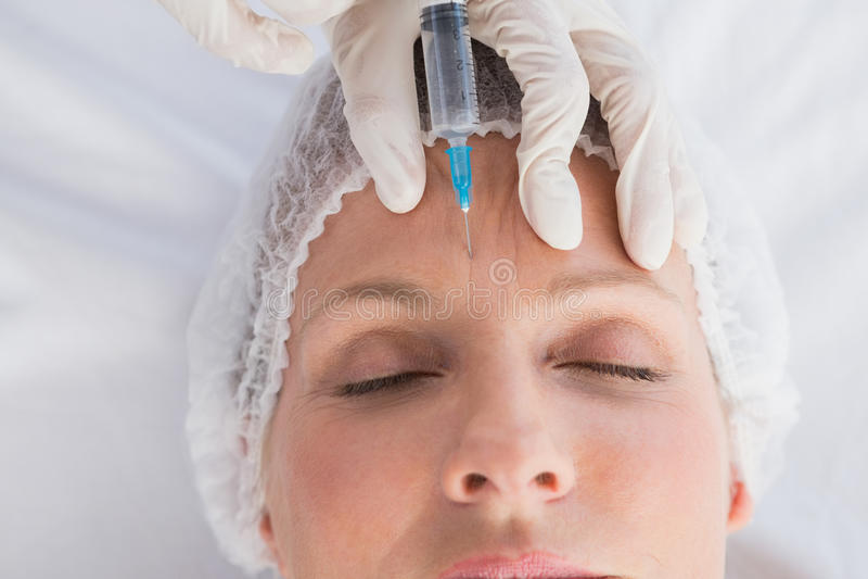 Injektion för kvinnahäleribotox på hennes panna arkivbild