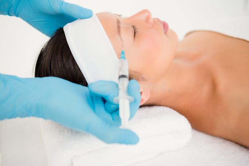 Injektion för kvinnahäleribotox på hennes panna royaltyfria foton