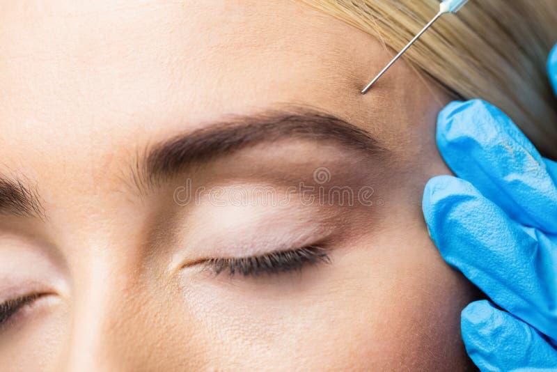 Injektion för kvinnahäleribotox på hennes panna royaltyfri foto