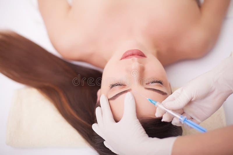 Injektion- och kvinnaskönhetframsida Attraktiv flicka med perfekt hud Kvinnan i brunnsort, masserar baksidan, slät hud Skönhet oc royaltyfria bilder
