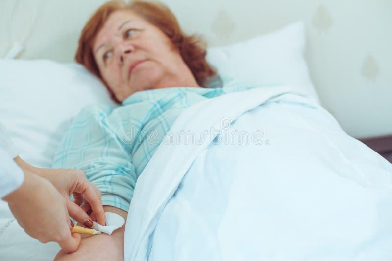 Injektion till den äldre kvinnan i sjukhus arkivbilder