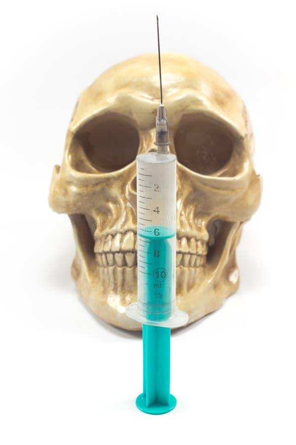 Injektionsspruta över den mänskliga skallen arkivfoton