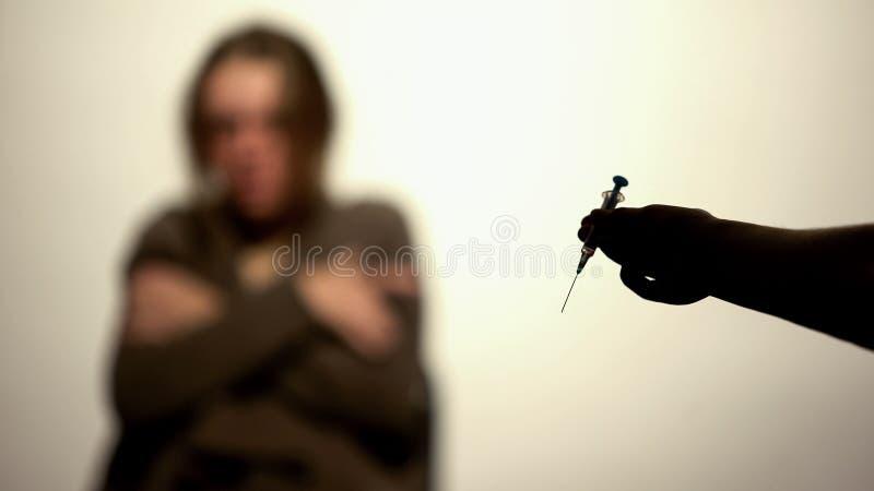 Injektionsspruta för dos för knarklangarehandinnehav på vit bakgrund, rehabtillbakadragande royaltyfri foto