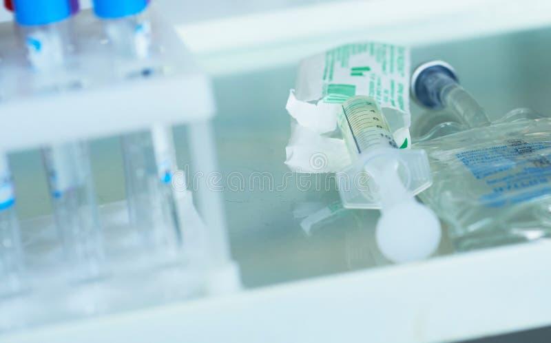 Injektionssprutan med drogen som är klar för injektion, ligger på tabellen för yttersidaexponeringsglasläkarundersökningen Viktig royaltyfri fotografi