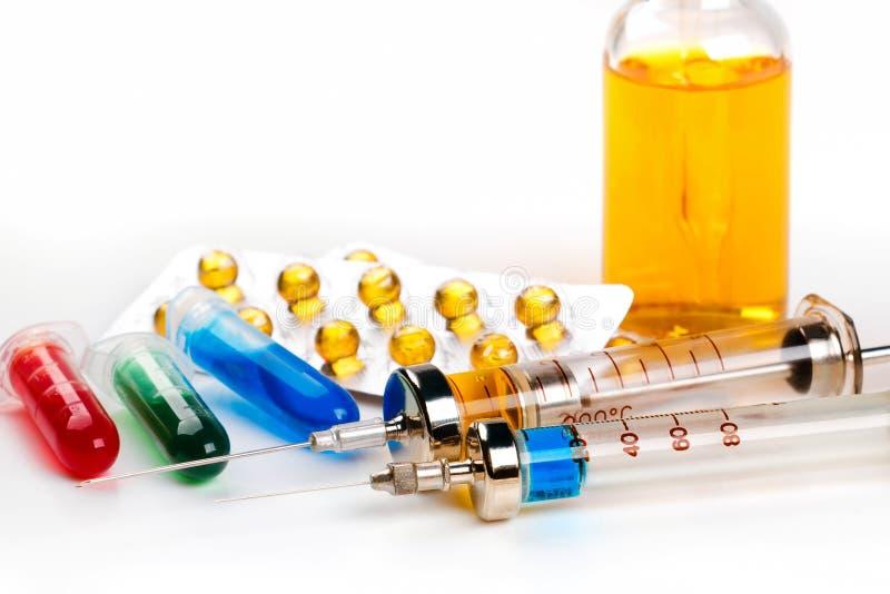 Injektionssprutor med läkarbehandlingen, blåsapacken, små medicinflaskor och flaskan med kulör vätska på vit bakgrund arkivfoton