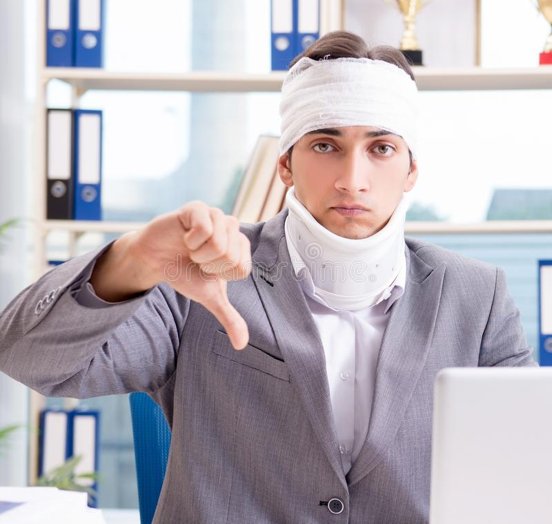 Injured businessman working in the office. The injured businessman working in the office stock image