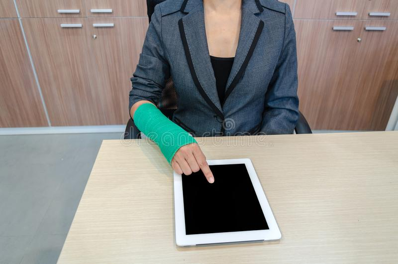 Injured businesswoman with broken hand and green cast on the wrist using tablet computer in office royalty free stock image