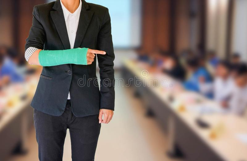 Injured businesswoman with green cast on hand and arm on blurred stock photo