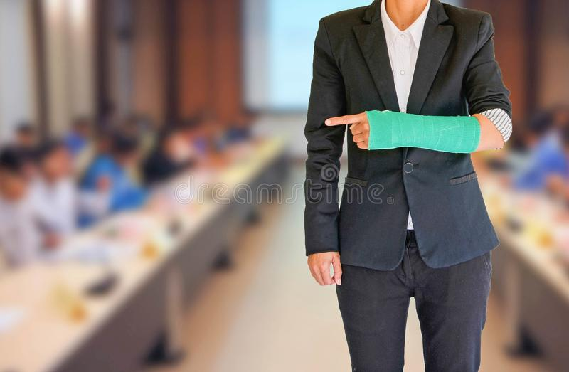 Injured businesswoman with green cast on hand and arm on blurred royalty free stock image