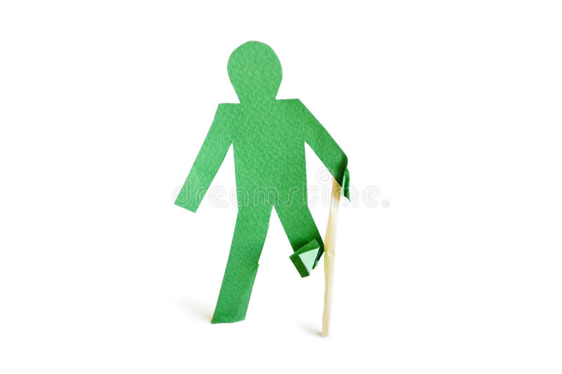 An injured green stick figure with a walking stick over white background royalty free stock images