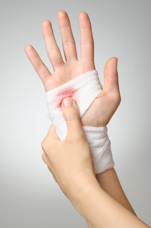 Injured hand with bloody bandage stock image