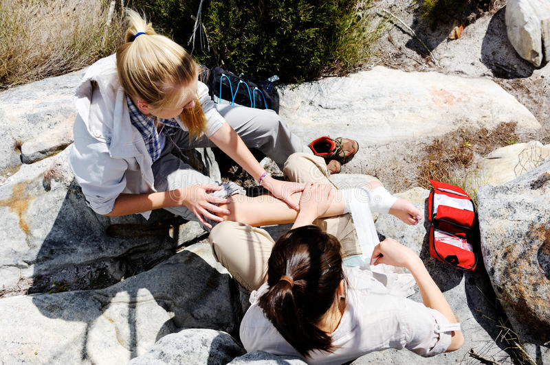 Injured hiker is tended to by her friend stock photos