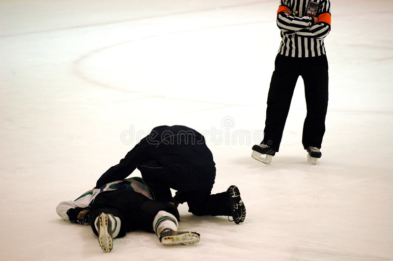 Injured hockey player. An injured ice hockey player being attended to on the ice stock photos