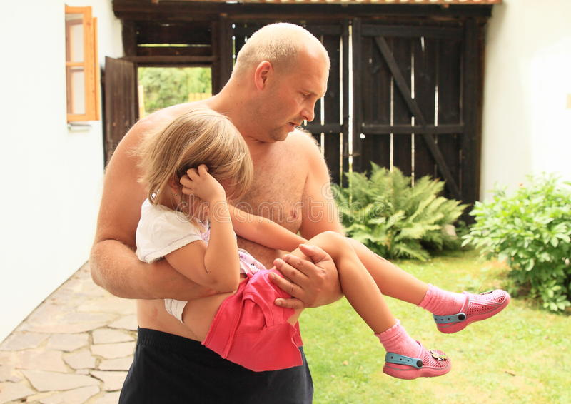 Injured little girl. Small child - little girl injured on leg and her father carrying her for medical care royalty free stock image