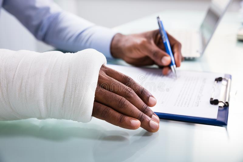 Injured Man Filling Insurance Claim Form. Overhead View Of Injured Man With Bandage Hand Filling Insurance Claim Form On Clipboard stock image