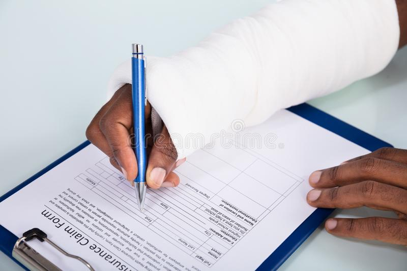 Injured Man Filling Insurance Claim Form. Overhead View Of Injured Man With Bandage Hand Filling Insurance Claim Form On Clipboard royalty free stock photo