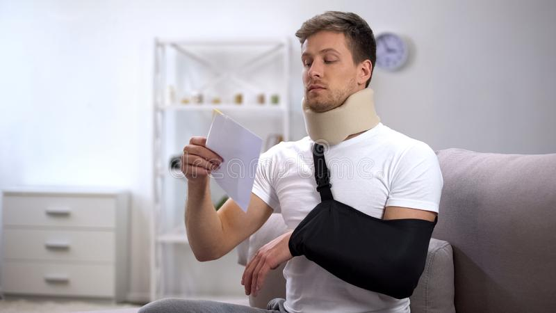 Injured man in foam cervical collar and arm sling trying to open envelope, bill royalty free stock image
