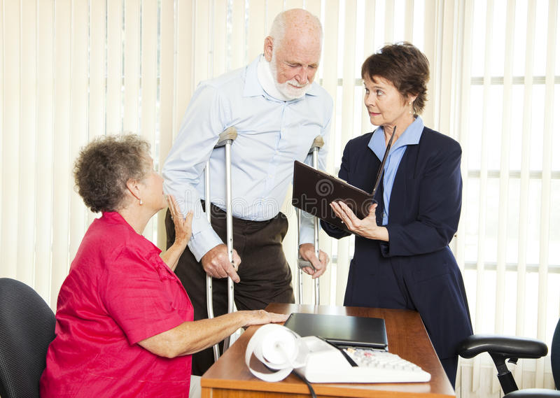 Injured Man with Lawyer. Injured man and his wife meet with a personal injury lawyer stock image