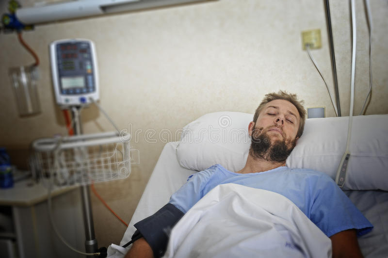 Injured man lying in bed hospital room resting from pain looking in bad health condition. Young injured patient man lying in bed hospital room resting from pain royalty free stock images