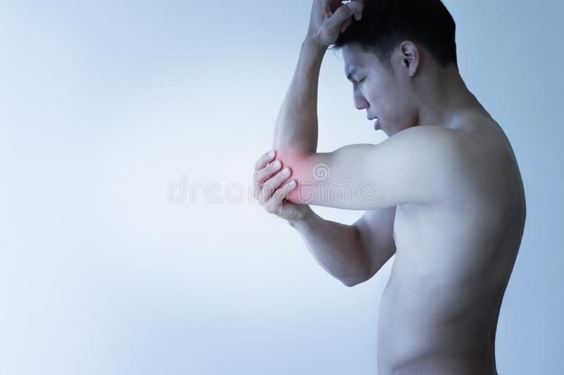 Injured man suffering from severe pain in elbow joint, red isolated. Elbow pain from a sports industry isolated in red on an Asian athlete royalty free stock photo