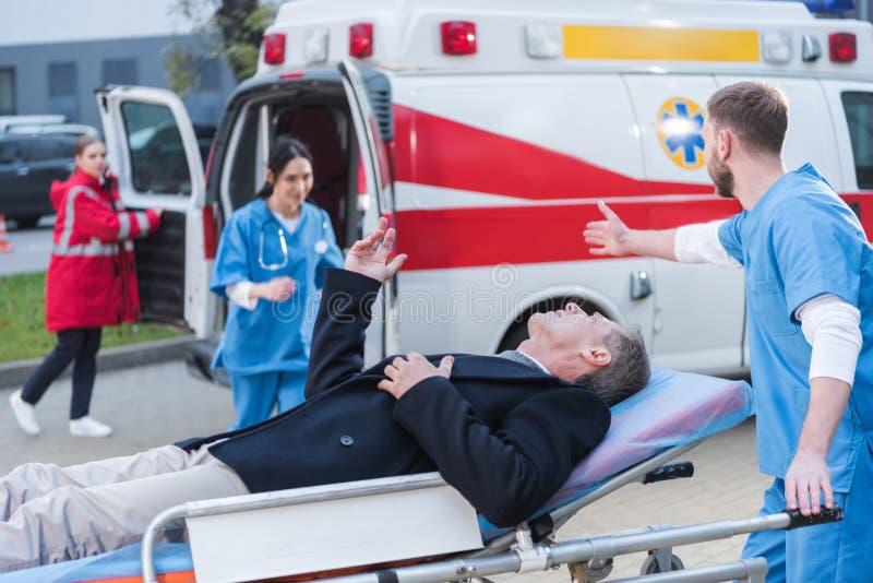 Injured man and doctor asking help of. Injured men and doctor asking help of other paramedic royalty free stock photo