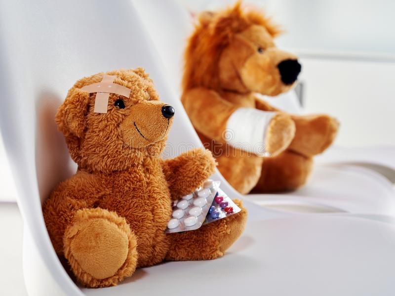 Injured teddy bear holding two medicine blisters royalty free stock images