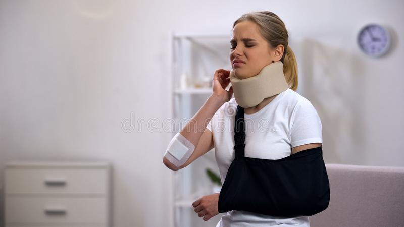 Injured woman in foam cervical collar and arm sling suffering pain in shoulder. Stock photo royalty free stock photo