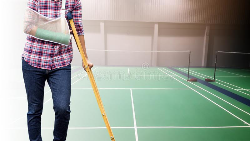 Injured woman with green cast on hand and arm on background badminton indoor court, sport accident pain concept stock images