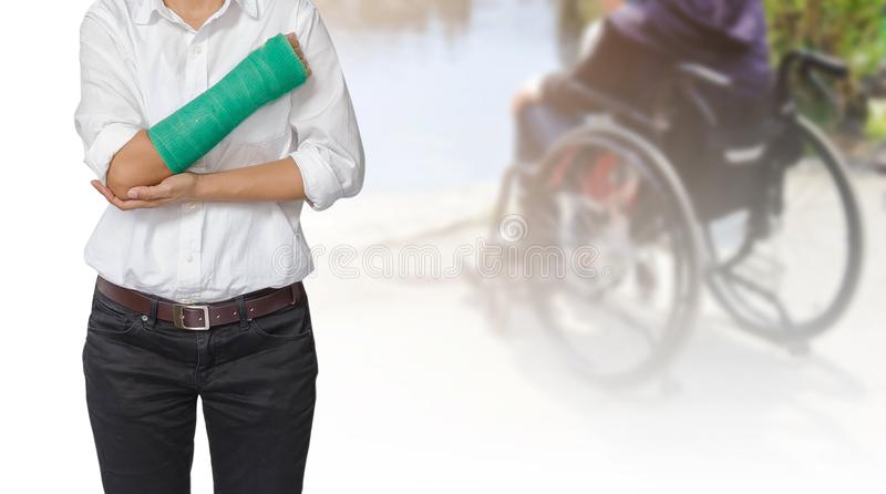 Injured woman with green cast on hand and arm on blurre royalty free stock photo