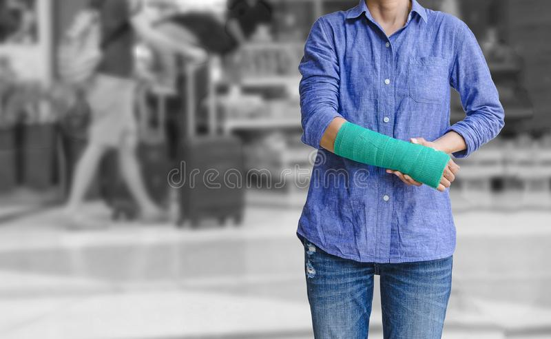 Injured woman with green cast on hand and arm on traveler in mot. Ion blur in airport interior background, Travel insurance concept royalty free stock images