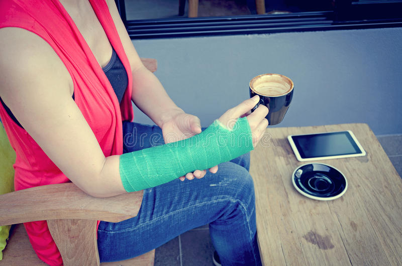 Injured woman with green cast on the wrist holding black coffee. Cup and smart phones on wood table in coffee cafe royalty free stock photography