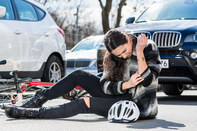 Injured woman sitting on the ground after bicycle accident stock images
