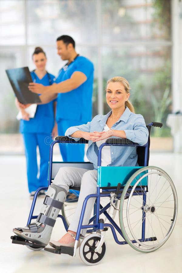 Injured woman wheelchair. Injured women on wheelchair with doctors at medical office stock photo