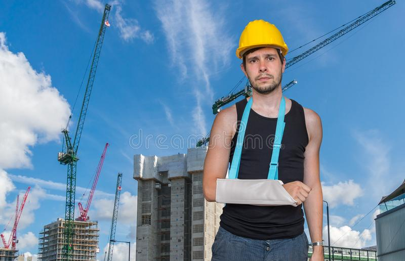 Injured worker is wearing medical sling on his arm. Construction site in background royalty free stock photo
