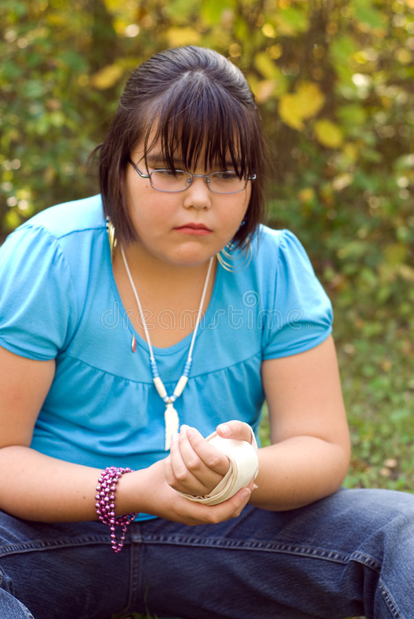 Injured Wrist. A nine year old girl holding her injured wrist and being brave with the pain stock photo