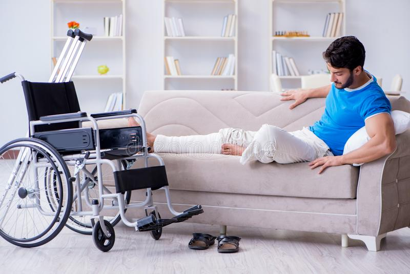 The injured young man recovering at home. Injured young man recovering at home royalty free stock photography