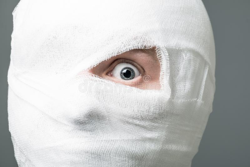 Man with bandage on his head. Injured young man after surgery with bandage all over his face with one eye opened. Image related with treatment of the wounds royalty free stock image