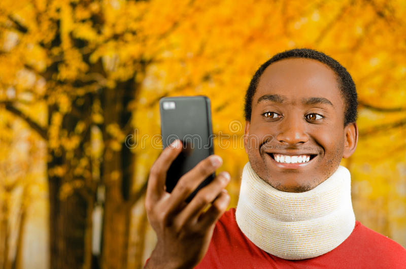 Injured young positive black hispanic male wearing neck brace and smiling, holding up cell phone as in taking selfie. Yellow abstract background royalty free stock photo