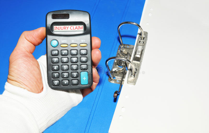 Injury claim. Concept with injured hand holding calculator royalty free stock photo