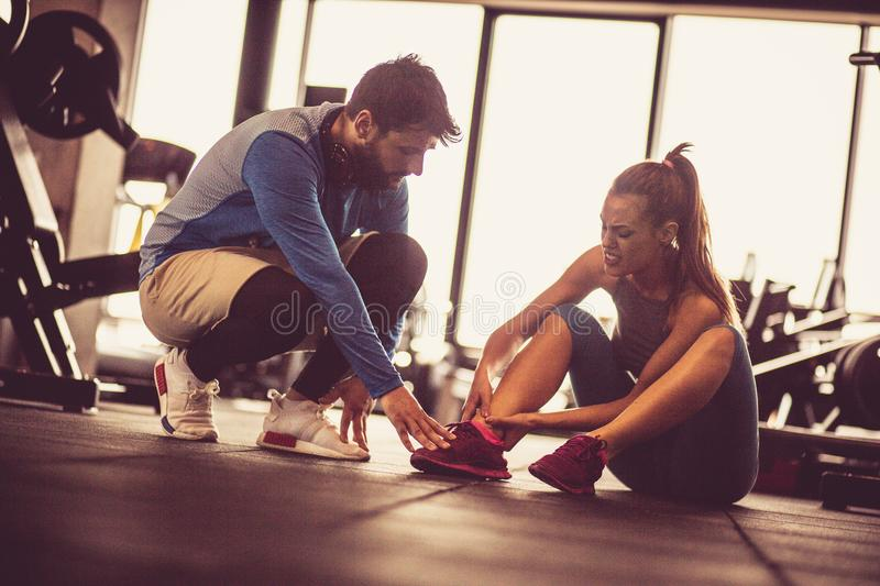 Injury at gym. Sportswoman with personal trainer in gym. Sports women having injury leg royalty free stock images