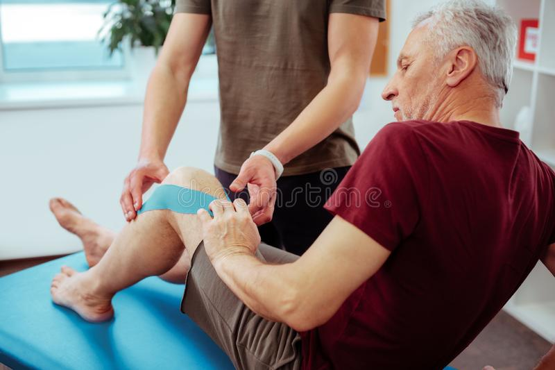 Nice elderly man having rehabilitation therapy course royalty free stock images