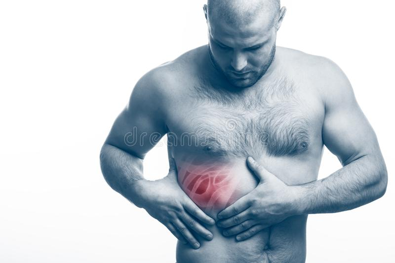 Injury of the rib. Young bald man sportive physique holds on sore rib isolated on white isolated background. Fracture of rib stock images
