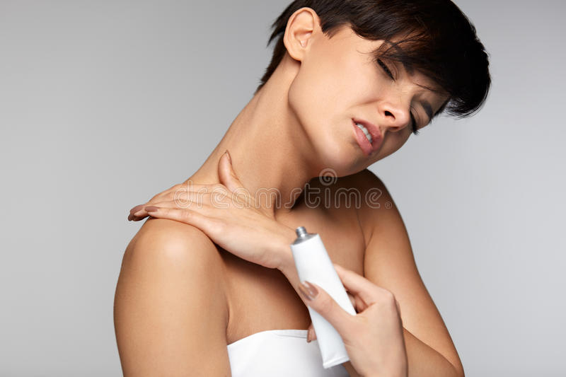 Injury Treatment. Beautiful Woman With Neck Pain Applies Cream royalty free stock photos