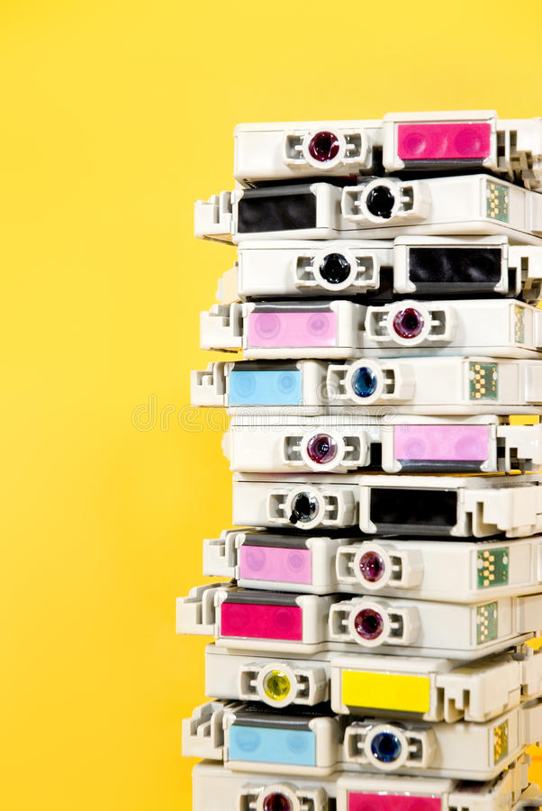Ink cartridges exhausted stacked on yellow background. Empty ink cartridges exhausted with labels of the four primary colors stacked on yellow background stock images