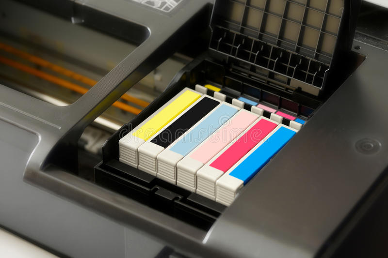 Ink cartridges in a printer. Row of individual ink cartridges in an office printer in CMYK colour palette stock image